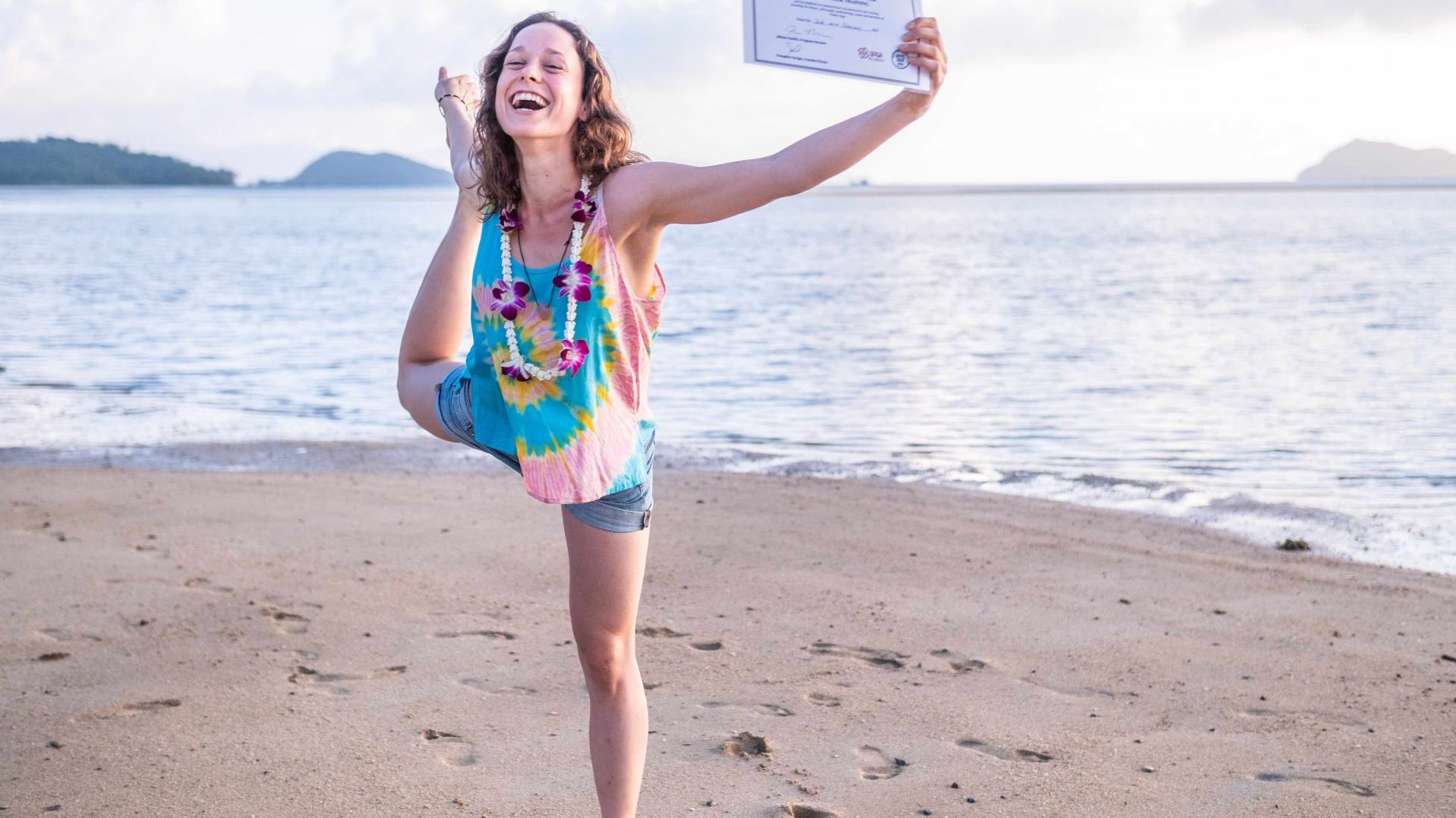 Happy yoga student celebrating her certification and smiling